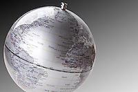 Close-up of silver globe over gray background