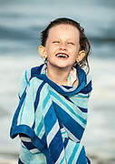 Young girl wrapped in a beach towel after swimming in the ocean.