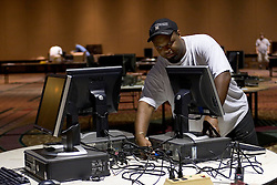 10 Sept 2005.  New Orleans, Louisiana.  Hurricane Katrina aftermath. <br /> Technician Courtney Kirklind sets up 100 computers ready for teams to get back to restoring functioning government.<br /> Photo; ©Charlie Varley/varleypix.com