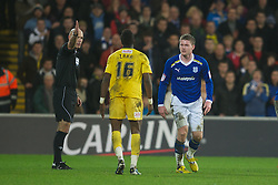 CARDIFF, WALES - Tuesday, January 24, 2012: Cardiff City's Aron Gunnarsson kicks out at Crystal Palace's Wilfried Zaha under the eye of referee Howard Webb, who misses the incident, during the Football League Cup Semi-Final 2nd Leg at the Cardiff City Stadium. (Pic by David Rawcliffe/Propaganda)
