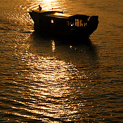 A boat silhoutted against the golden sunset on the Perfume River in Hue, Vietnam.