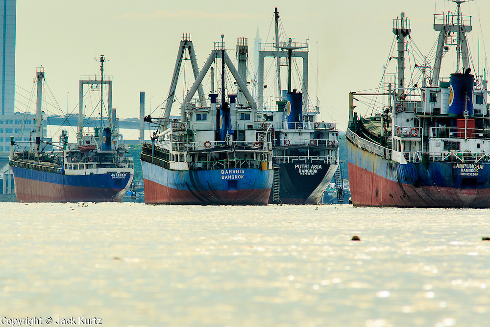 """17 NOVEMBER 2012 - BANGKOK, THAILAND:  Ocean freighters tied up in Klong Toey Port in Bangkok. Klong Toey has served as Bangkok's deep water port for centuries, but as ships have gotten bigger and Thailand's role in the world economy has expanded most of the commercial shipping has moved to ports closer to the ocean. Bangkok used to be known as the """"Venice of the East"""" because of the number of waterways the criss crossed the city. Now most of the waterways have been filled in but boats and ships still play an important role in daily life in Bangkok. Thousands of people commute to work daily on the Chao Phraya Express Boats and fast boats that ply Khlong Saen Saeb or use boats to get around on the canals on the Thonburi side of the river. Boats are used to haul commodities through the city to deep water ports for export.    PHOTO BY JACK KURTZ"""
