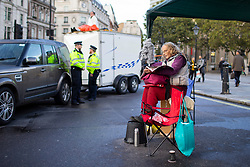 © Licensed to London News Pictures. 08/10/2019. London, UK. An Extinction Rebellion protester ties herself to a gazebo in Trafalgar Square . Photo credit: George Cracknell Wright/LNP