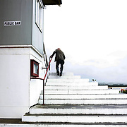 An elderly gentleman climbs the steps into the grandstand the Winton Harness Racing Club Race meeting at the Central Southland Raceway, WInton, Southland, New Zealand. 10th February 2012. Photo Tim Clayton