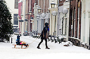 Een vrouw loopt met een kind op de slee achter haar aan in de sneeuw over de Oudegracht in Utrecht.<br /> <br /> A woman is walling with a child on a sled at the Oudegracht in Utrecht.