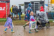Day arrivals come well prepared for the rain. The 2015 Glastonbury Festival, Worthy Farm, Glastonbury.