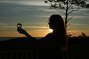 Red haired woman holding crystal ball at sunrise