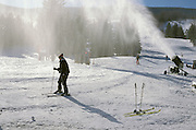 Person skiing past a snowmaking device