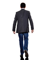 one caucasian business man walking rear view in silhouette on white background