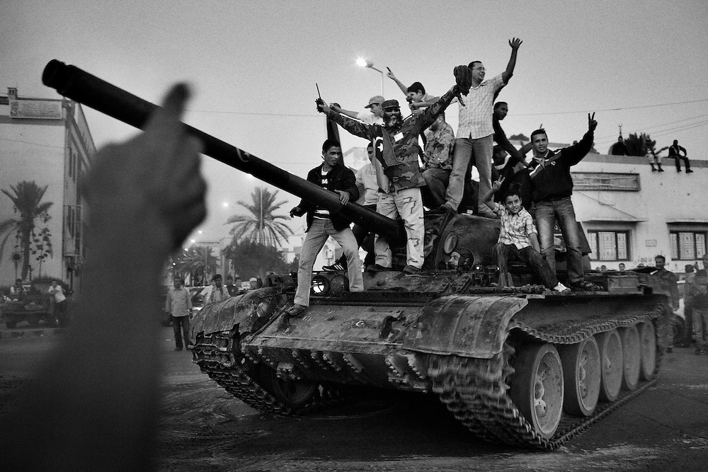 Supporters of anti-Qaddafi rebels celebrate their victory atop of a tank following a military parade at Freedom Square in Misurata, on October 28, 2011, Libya. Photo by Mauricio Lima for The New York Times