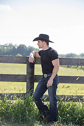 sexy cowboy leaning against a spilt rail fence