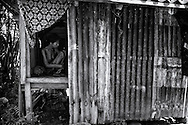 This little metal cage away from the main house has been Sari's prison for over sixteen years,  when she became mentally ill she got placed in this tin shed with only a woven bamboo floor to sit on and empty inside. Here she is sitting in a position hardly changed over all these years. Now she is not able to walk anymore. ©Ingetje Tadros/Diimex<br /> Publishing Rights www.diimex.com Bali,Indonesia