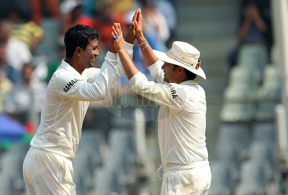 Pragyan Ojha of India and Sachin Tendulkar of India celebrate during day one of the second Star Sports test match between India and The West Indies held at The Wankhede Stadium in Mumbai, India on the 14th November 2013<br /> <br /> This test match is the 200th test match for Sachin Tendulkar and his last for India.  After a career spanning more than 24yrs Sachin is retiring from cricket and this test match is his last appearance on the field of play.<br /> <br /> <br /> Photo by: Ron Gaunt - BCCI - SPORTZPICS<br /> <br /> Use of this image is subject to the terms and conditions as outlined by the BCCI. These terms can be found by following this link:<br /> <br /> http://sportzpics.photoshelter.com/gallery/BCCI-Image-Terms/G0000ahUVIIEBQ84/C0000whs75.ajndY