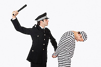 Side view of police officer with nightstick arresting male prisoner against gray background