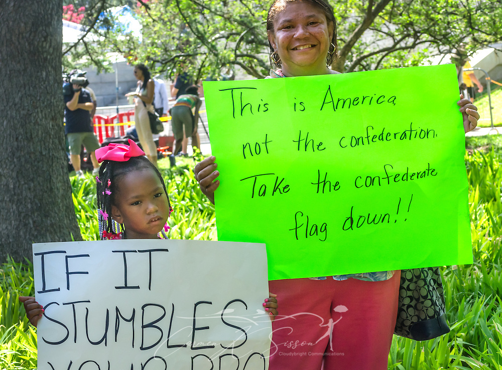 A mother and daughter hold signs supporting the removal of the Confederate flag from the South Carolina State House, July 10, 2015, in Columbia, S.C. Area garages and parking spaces filled quickly as thousands flocked to the South Carolina Statehouse to see the removal of the  Confederate flag. The flag flew above the capitol dome from 1961-2000, then was moved to the grounds. The flag, which is now permanently removed, will be stored at the Confederate Relic Room and Military Museum. The House voted for its removal after the shooting of nine African-Americans at Emanuel African Methodist Episcopal Church in Charleston, June 17, 2015. Alleged shooter Dylann Roof, who published a manifesto on his website supporting white supremacist beliefs, was seen in numerous photographs holding the Confederate flag. (Photo by Carmen K. Sisson/Cloudybright)