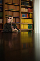 Man wearing suit at desk in library portrait