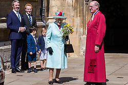 Windsor, UK. 21st April 2019. The Queen prepares to leave after being presented with a traditional posy of flowers by local schoolchildren outside St George's Chapel in Windsor Castle following the Easter Sunday service.