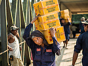 27 OCTOBER 2015 - YANGON, MYANMAR:  Men load rum and other products onto a freighter at a pier along the Twante Canal in Yangon.   PHOTO BY JACK KURTZ