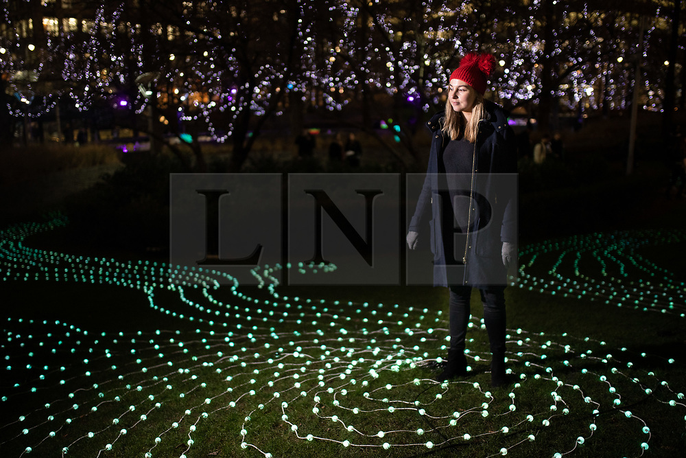 © Licensed to London News Pictures. 14/01/2019. London, UK. Martine Basson looks at 'Flow' a light installation created by Squidsoup as part of Canary Wharf's Winter Lights 2019. Photo credit : Tom Nicholson/LNP
