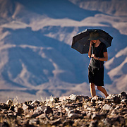 Maria keeps the sun off her Swedish skin with the make shift parasol. This is Fish River Canyon, Nambia.