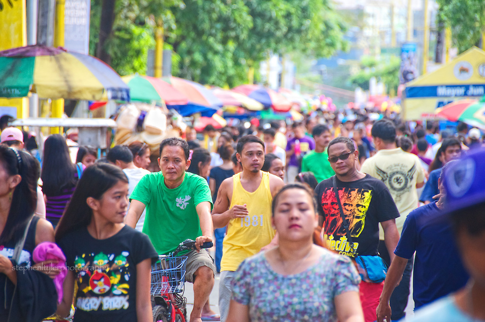 Crowds in the streets during the celebration of traditional All Saints Day (Halloween) in Makati City's Manila South Cemetery, where friends and family of the departed visit gravesites and spend time (sometimes all night into the following day) to eat and reflect on long lost loved ones.
