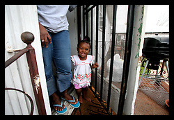 09 July 2006 - New Orleans - Louisiana. Finding Faith. Faith Figueroa. A day in the life of. Faith stands at her mother Miriam's feet at the security enhanced entrance to their apartment in the devastated 9th ward. <br />Following a ten month search for the little girl whose face appeared on the Sept 19th, 2005 cover of Newsweek magazine, Faith's mother, Miriam Figueroa has returned to town with her three children. Faith, (1 yrs), Anfernya (5yrs) and Jacquelyn (13 yrs). Credit; Charlie Varley/Sipa Press.