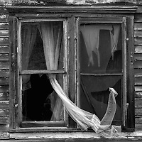 Abandoned house with curtain in broken window in Berwick, McHenry County USA