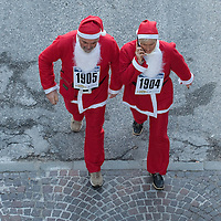 NOALE, ITALY - DECEMBER 18:  Two participants  dressed as Father Christmas are seen from above as they take part in the Noale Santa Run on December 18, 2011 in Noale, Italy. Close to two thousand people participated in the third annual Noale Santa Run, one of the largest non competitive Santa Run in Italy.