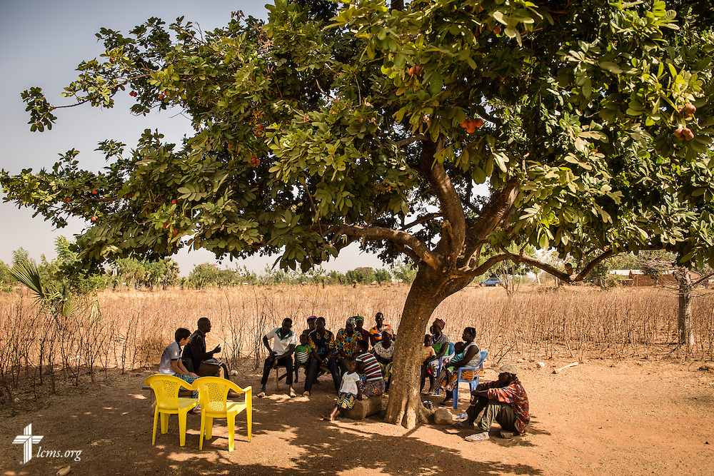 The Rev. Remi Lare Lambon, pastor in the Lutheran Church of Togo, shares a devotion with villagers on Tuesday, Feb. 14, 2017, at a rural home in Sankpong, Togo. He is joined by Valerie Stonebreaker, LCMS missionary to Togo. LCMS Communications/Erik M. Lunsford