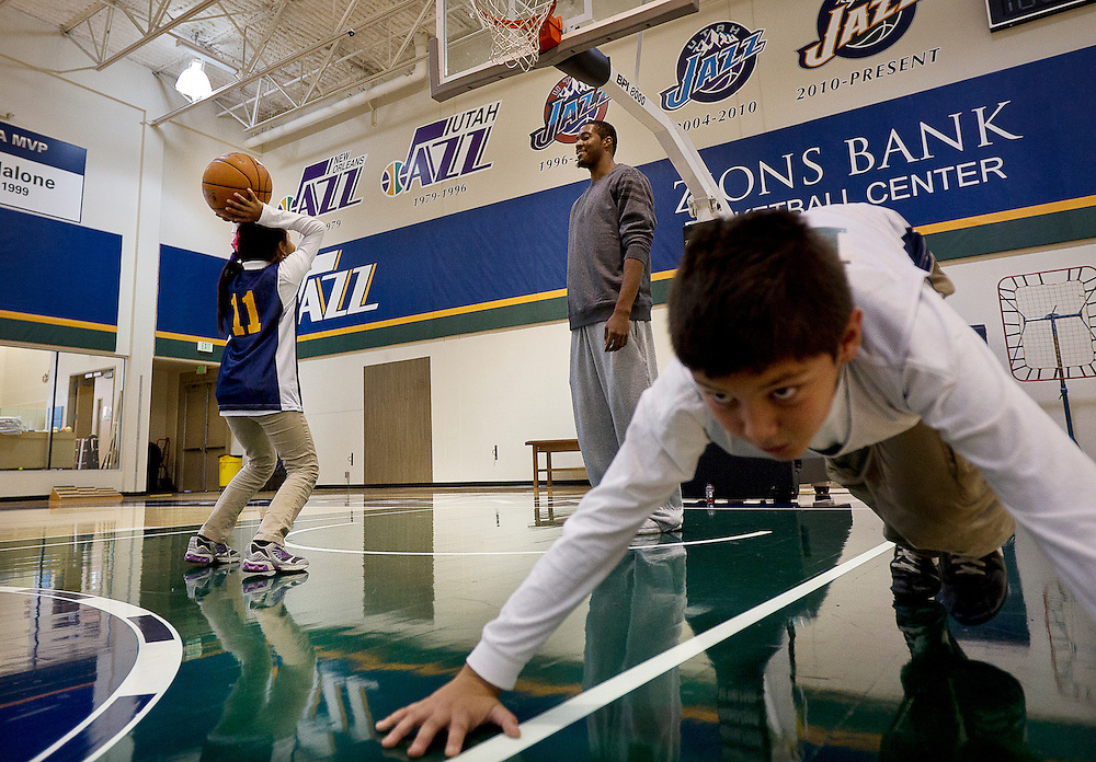 Utah Jazz player Derrick Favors, center, coaches free throws as Cesar Velazquez, right, does pushups during a private basketball clinic for local at-risk youth from the Dream Academy at the Zions Bank Basketball Center, Wednesday, Oct. 24, 2012.