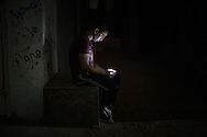 A young man sitting in a street in total darkness is texting on his cell phone during a blackout. Un giovane in una strada totalmente buia scrive col proprio cellulare durante un blackout.