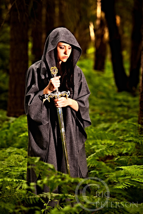 Mysterious cloaked woman in forest