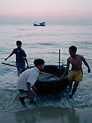 Boys pulling a bamboo coracle on shore.