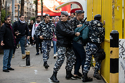 ©2020 Tom Nicholson. 11/01/2020. Beirut, Lebanon. Police detain an anti-government demonstrator, outside 'Electricité du Liban', the main Lebanese electricity provider. Demonstrators are taking part in a protest march from Daoura in east Beirut to Parliament in Downtown Beirut. The demonstrations are part of a wider movement which started in mid October 2019, campaigning against government corruption and economic crisis. Photo credit : Tom Nicholson