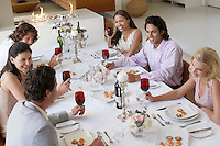 Friends sitting together at Dinner Party drinking and socialising elevated view
