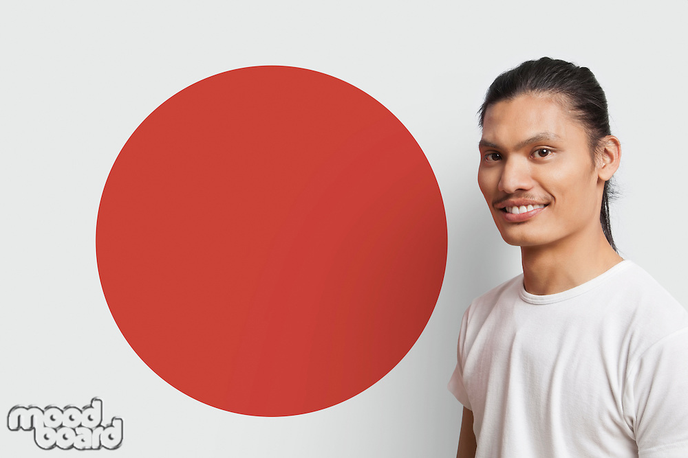 Portrait of young Asian man smiling against Japanese flag