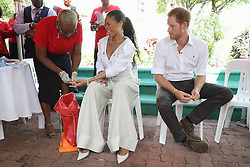 Rihanna (centre) and Prince Harry take part in a live HIV test, at the 'Man Aware' event held by the Barbados National HIV/AIDS Commission in Bridgetown, Barbados, during his tour of the Caribbean.