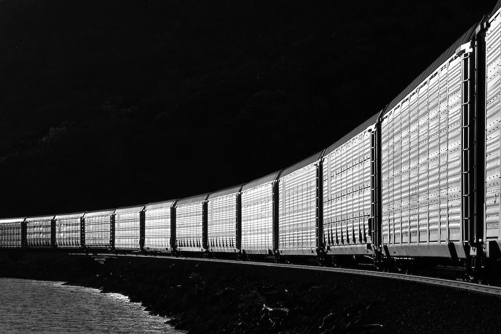 A morning auto rack train heads south along the Hudson River.