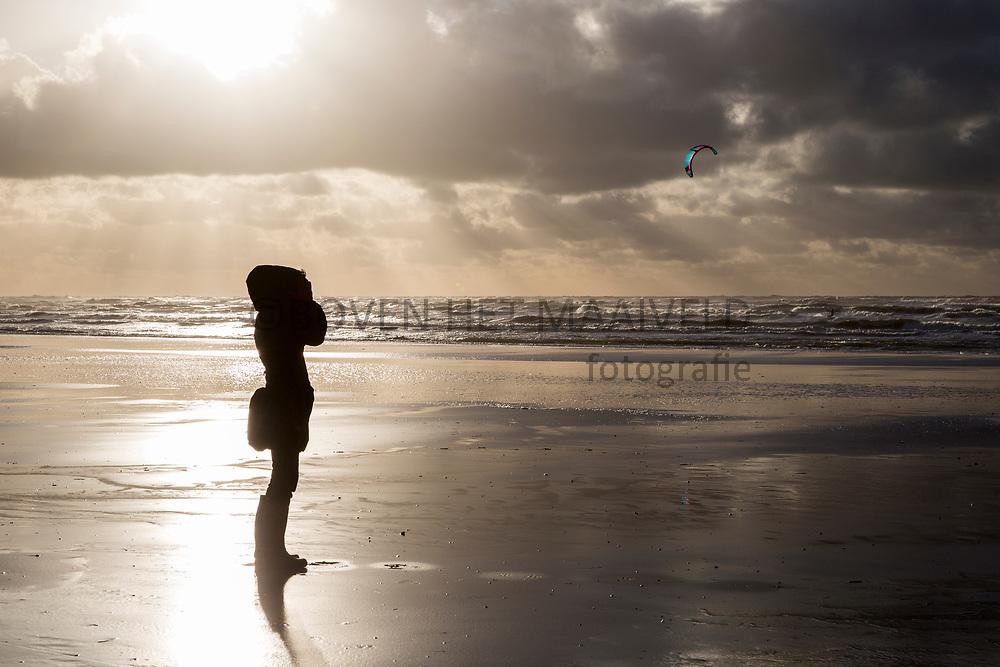 IJmuiden, herfststorm met strandwandelaar en surfer.