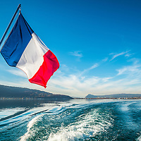 Tricolour flying from the stern of a pleasure boat on Lac d'Annecy, France