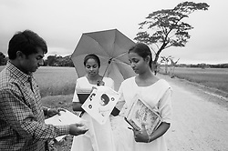 BANGLADESH NETRAKONA DURGAPUR 17OCT00 - Our friend and translator, Mr MD Abdul Jabber, hands out leaflets to local high-school girls who promised to spead our appeal for information. Numerous people came forward upon the news of our presence, claiming to be Lisa's parents. However, we verified that most people's stories were either fabricated or did not otherwise match the details of Lisa's case. ..jre/Photo by Jiri Rezac..© Jiri Rezac 2000..Tel/Fax: +44 (0) 20 8968 9635.Mobile: +44 (0) 7801 337 683..Email: jiri@jirirezac.com.Web: www.jirirezac.com..All pictures © Jiri Rezac 2000. All rights reserved.