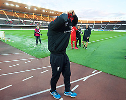 HELSINKI, FINLAND - Friday, July 31, 2015: Liverpool's manager Brendan Rodgers takes off his training top during a walk around the pitch after the 2-0 victory over HJK Helsinki during a friendly match at the Olympic Stadium. (Pic by David Rawcliffe/Propaganda)