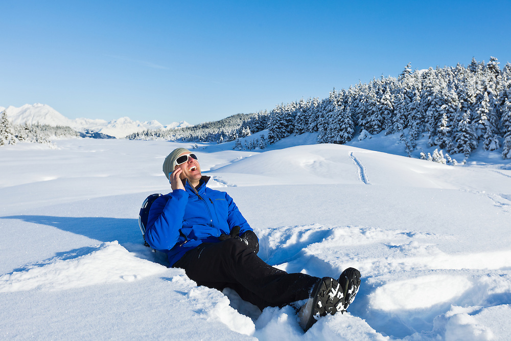 A hiker reclines against his snowshoes while talking on a cellphone on a sunny blue-sky day at Turnagain Pass with the Chugach Mountains in the background in the Chugach National Forest of Southcentral Alaska. Winter. Afternoon. MR.