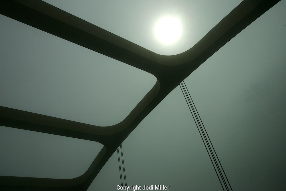 Looking up through the beams of a bridge on a foggy day.