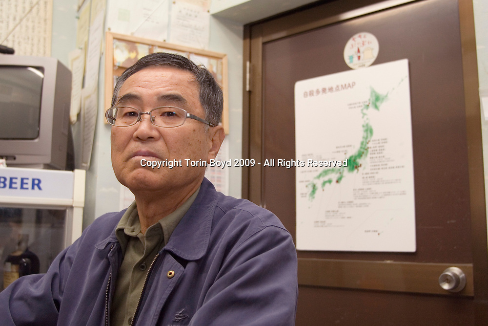 Nov. 26, 2009, Sakai City: This is 66 year old Isao Saito, a retired police officer from Fukui Prefecture who patrols the rocky cliffs at Tojinbo for possible suicides attempts. He is seen here at the suicide NPO office in Tojinbo on November 26, 2009. Behind him is a suicide map of Japan. Mr. Saito is a member of the NPO suicide prevention group Kokoro ni Hibiku Bunshu Henshukyoku, which was founded by 65 year old Yukio Shige (pronounced shee-gay), a retired policeman from Fukui Prefecture who took up his cause in 2004, just before retirement as a police deputy at a nearby police station. When Shige discovered how many suicides were occurring here, he began patrolling the cliffs of Tojinbo in order to spot those contemplating suicide. Upon retirement Shige opened a small cafe at Tojinbo where he also set up his NPO. Since then other volunteers like Mr. Saito have joined his cause and as of November 2009, he and his group have talked 222 out of committing suicide. They do this by patrolling the cliffs daily with binoculars in hand, and when they spot someone they kindly approach them and coax them away to Shige's cafe where they offer them tea and rice cakes. They also see these people home safely, and in cases where an individual is homeless, they find hem accommodations. However there are still some that slip past their watchful eyes and so far in 2009 thirteen people have jumped to their deaths here. Japan has one of the highest suicide rates in the world and 2009 may surpass the record 34,427 deaths that occurred here in 2003. This increase is thought to be a result of the Japanese recession which has been worsened by the global economic downturn. Depression is the number one cause for suicide in Japan, followed by illness and debt. Photo by Torin Boyd.