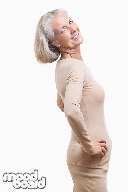 Side view of senior woman in casuals with hands on hips against white background