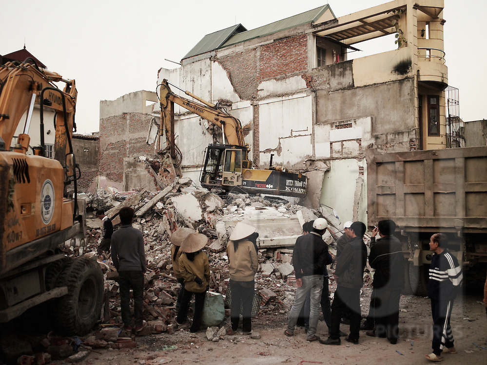 Vietnamese people gather around an excavator demolisihing houses in Hoang Hoa Tham street, Hanoi, Vietnam, Asia