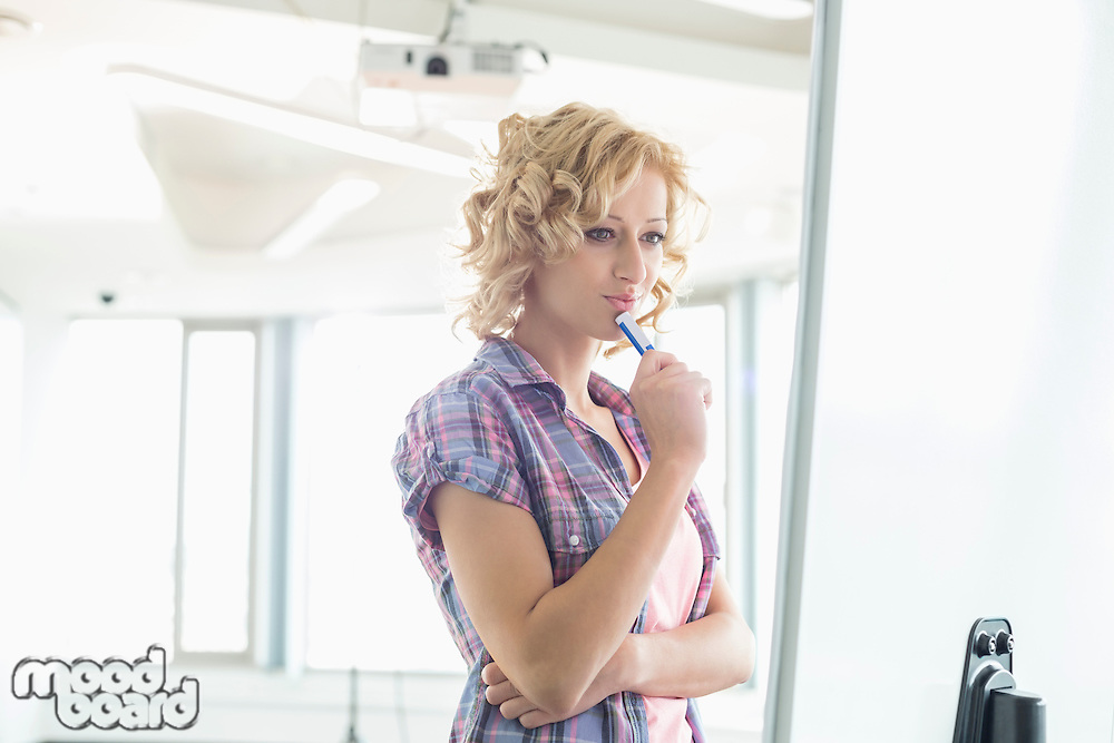 Concentrated businesswoman looking at presentation board in creative office