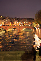 Local men talking on a bridge over the River Seine in Paris, France, Europe.