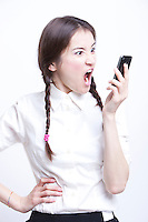 Furious young woman screaming into her cell phone against white background